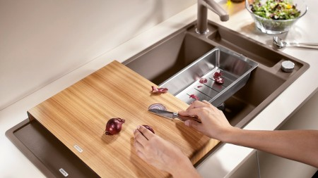 Onions are cut on a cutting board at a BLANCO sink