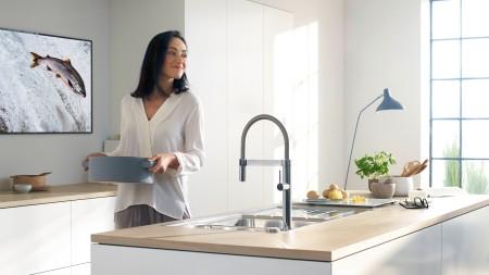 Eine Frau steht vor einer BLANCO Spüle und hat einen Kochtopf in der Hand