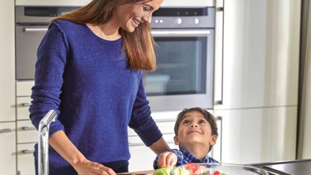 Eine Frau und ein kleiner Junge stehen zusammen in der Küche und kochen
