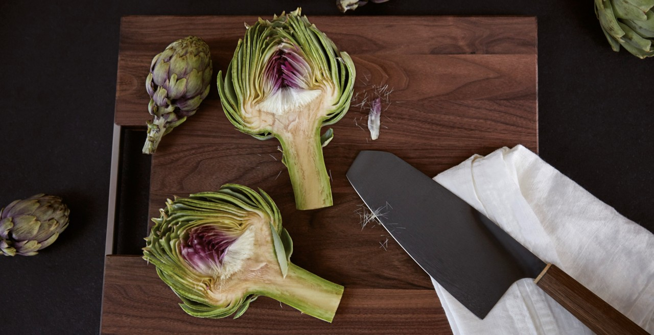 A halved artichoke on a dark chopping board