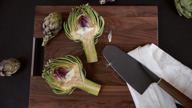 A pointed artichoke on a dark chopping board