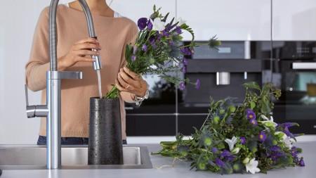 A woman fills a dark grey vase and arranges purple flowers inside