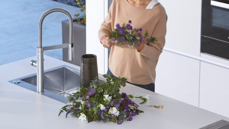 A woman is holding a bunch of purple flowers