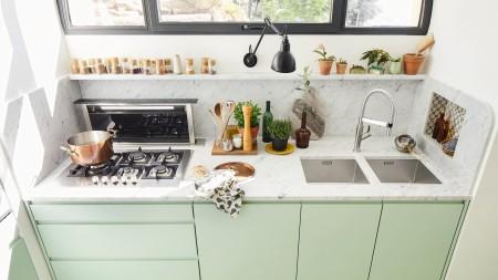 Blick auf eine Küchenzeile mit Herd, Arbeitsbereich und Spüle.