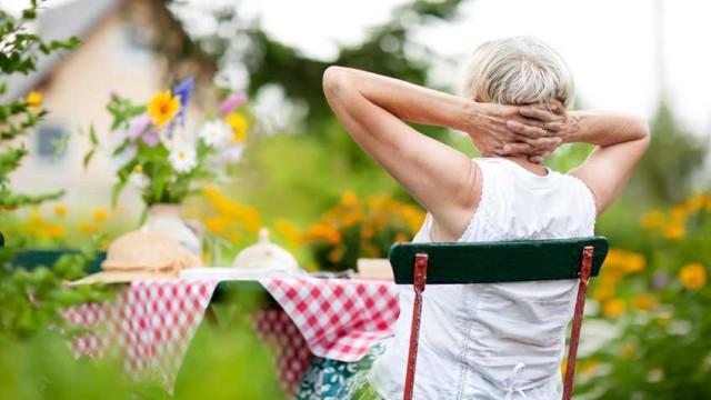 eine alte Dame sitzt im Garten