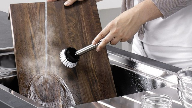 A dark cutting board is cleaned in a stainless steel sink