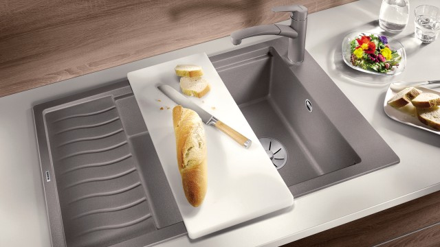 A baguette on a white plastic cutting board on a Silgranit sink