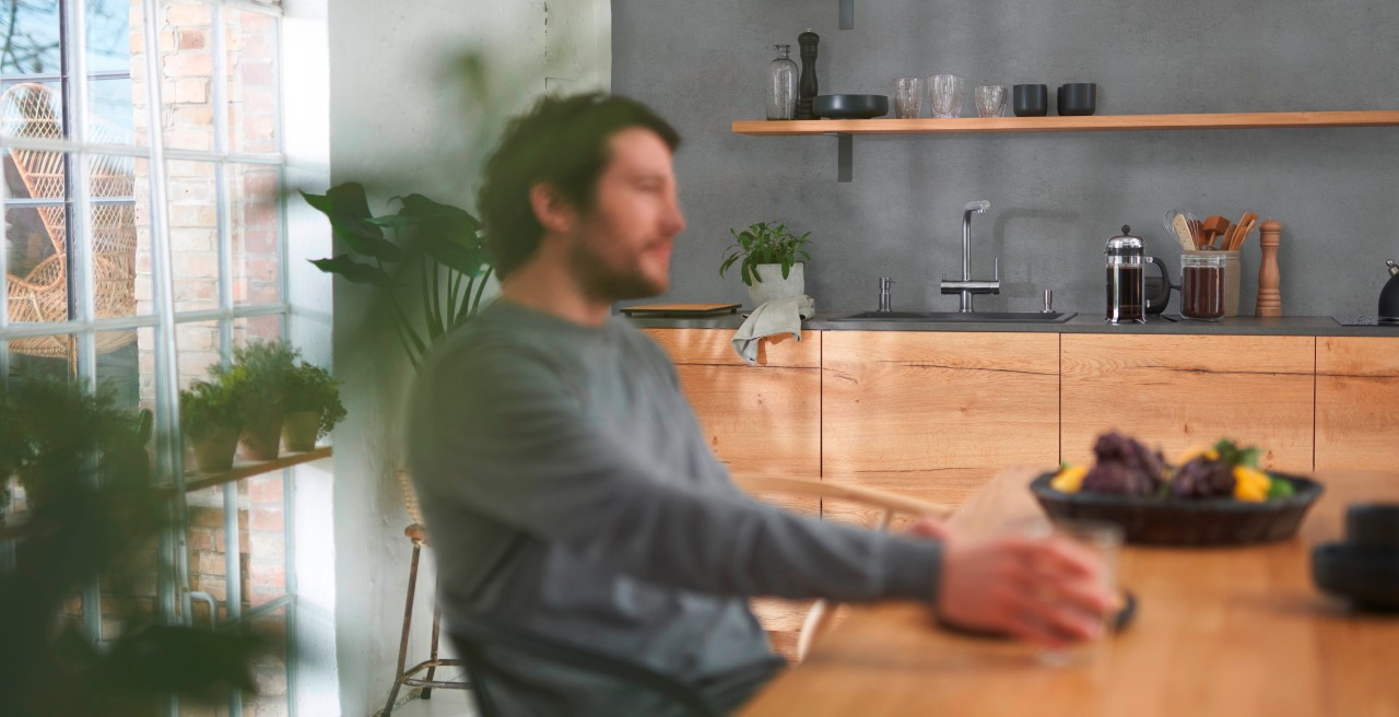 Man sitting at dining table in front of kitchen water hub