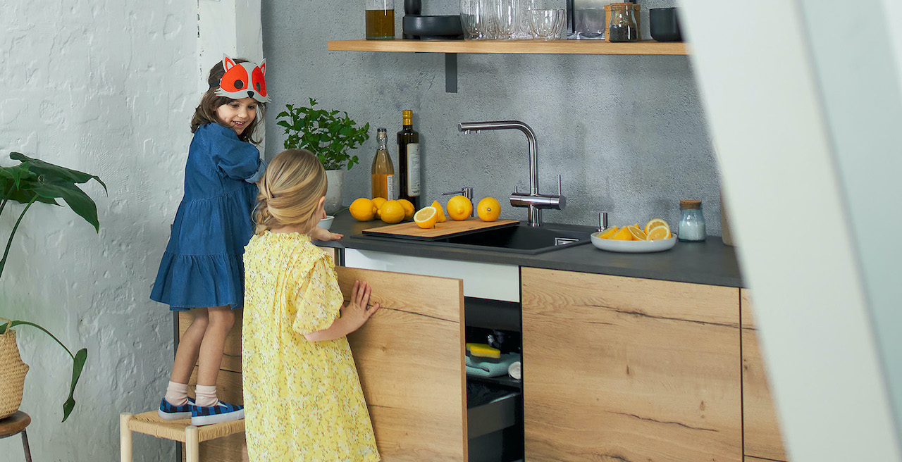 Kids are playing in the kitchen at the kitchen water hub from BLANCO