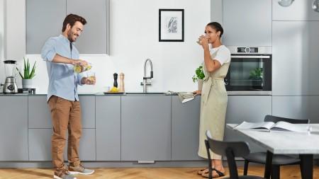 Ein Mann gießt sich frisches Wasser ein, eine Frau trinkt aus einem Glas