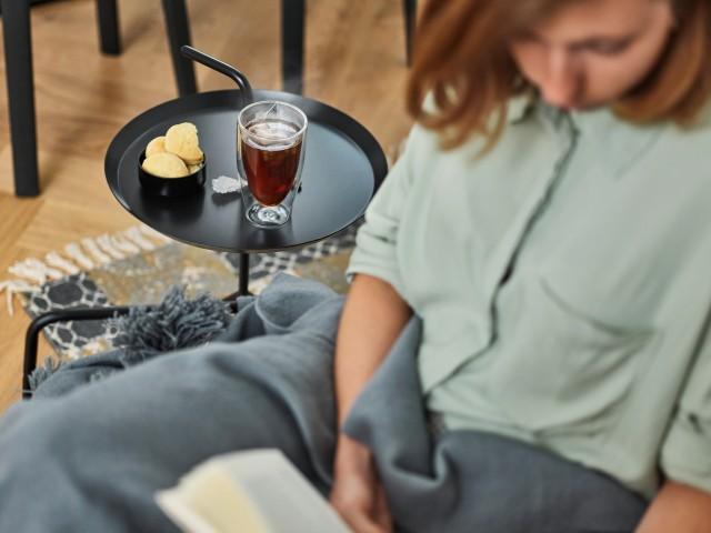 Eine Frau liest ein Buch und genießt dabei einen heißen Tee