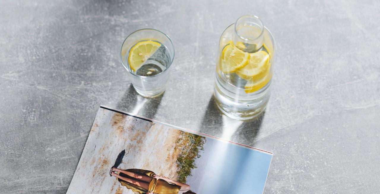 Ein Glas frisches Wasser steht auf einer grauen Arbeitsplatte