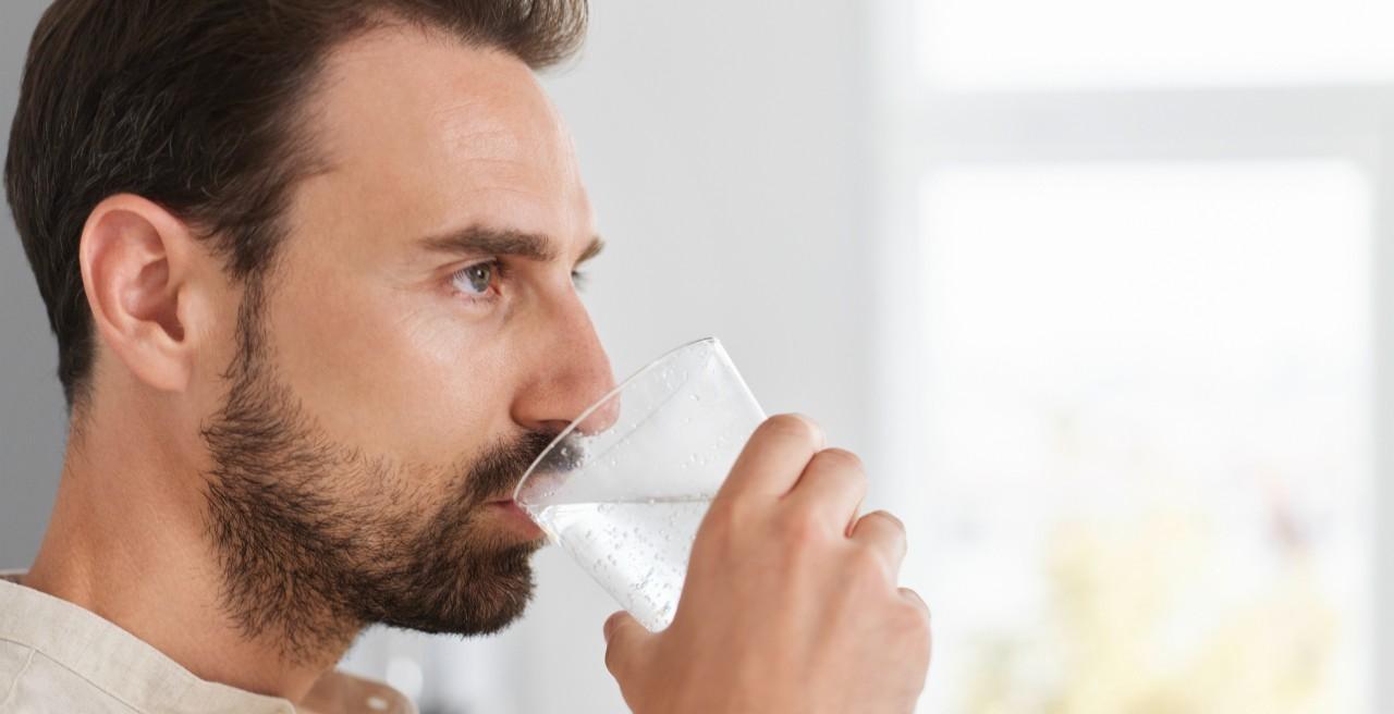 Ein Mann trinkt ein Glas Soda Wasser aus einer BLANCO Armatur