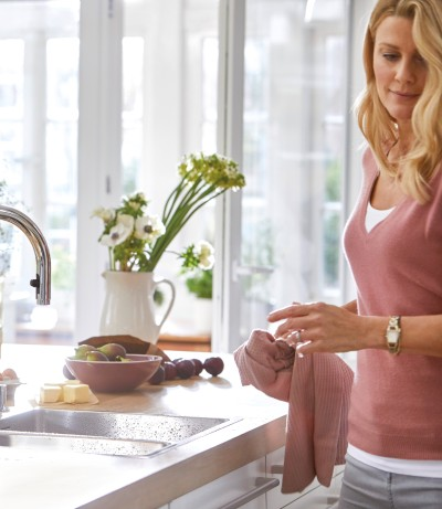 a woman standing in front of a BLANCO sink