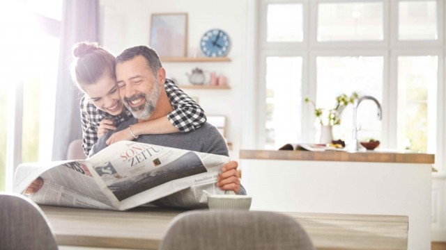 A girl hugs her father, who is sitting at a table reading a newspaper