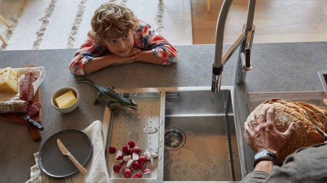 A boy watches his father curiously cut bread at a BLANCO stainless steel sink