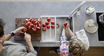 A father and his son are washing and cutting tomatos