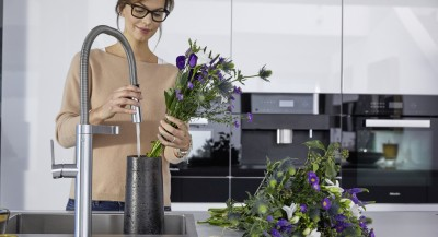 a woman is arranging flowers in a BLANCO stainless steel sink