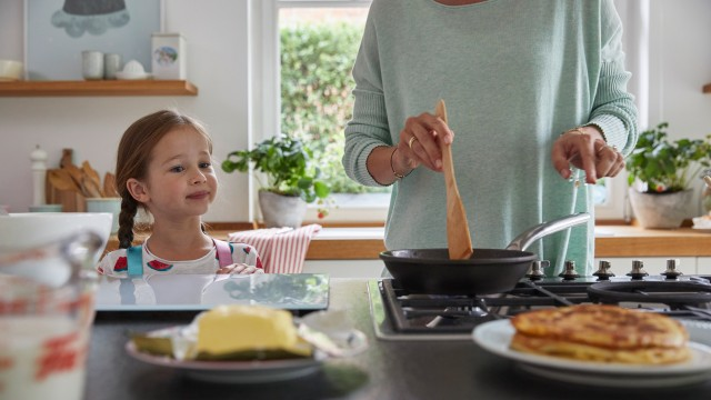 A young girl makes pancakes with her mother