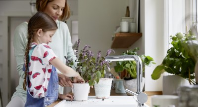 a girl and a woman are repotting a plant on a white silgranit sink