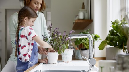 A child repotting a plant on a white Silgranit sink
