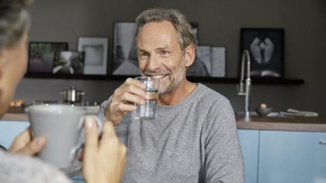 A man drinks a glass of water and smiles