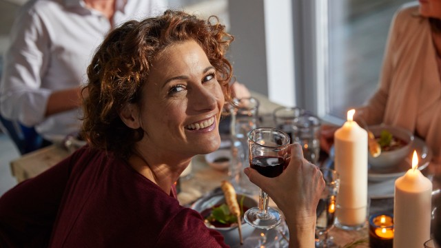 A woman looks happily into the camera and holds a wine glass in her hand