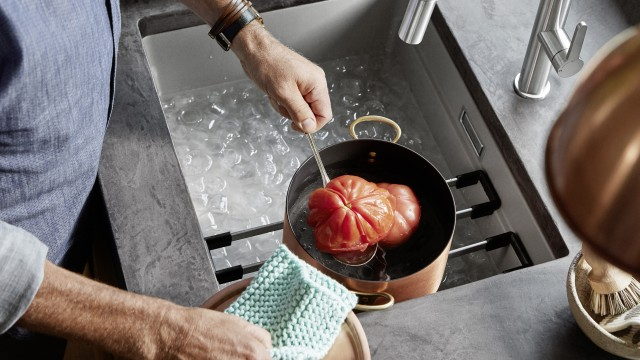 A man is blanching a tomato