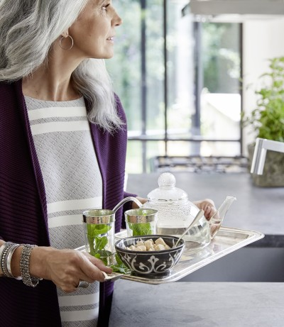 A woman holds a tray of tea in her hands