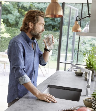 a man drinking a glas of water
