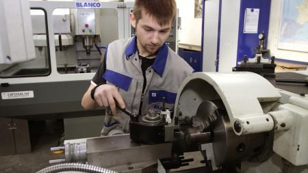 Auszubildender an der Sägemaschine in der Produktion