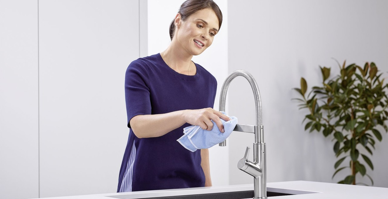 Woman cleaning her stainless steel faucet