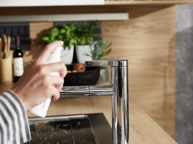 Armatur mit Reinigungamittel besprühen
