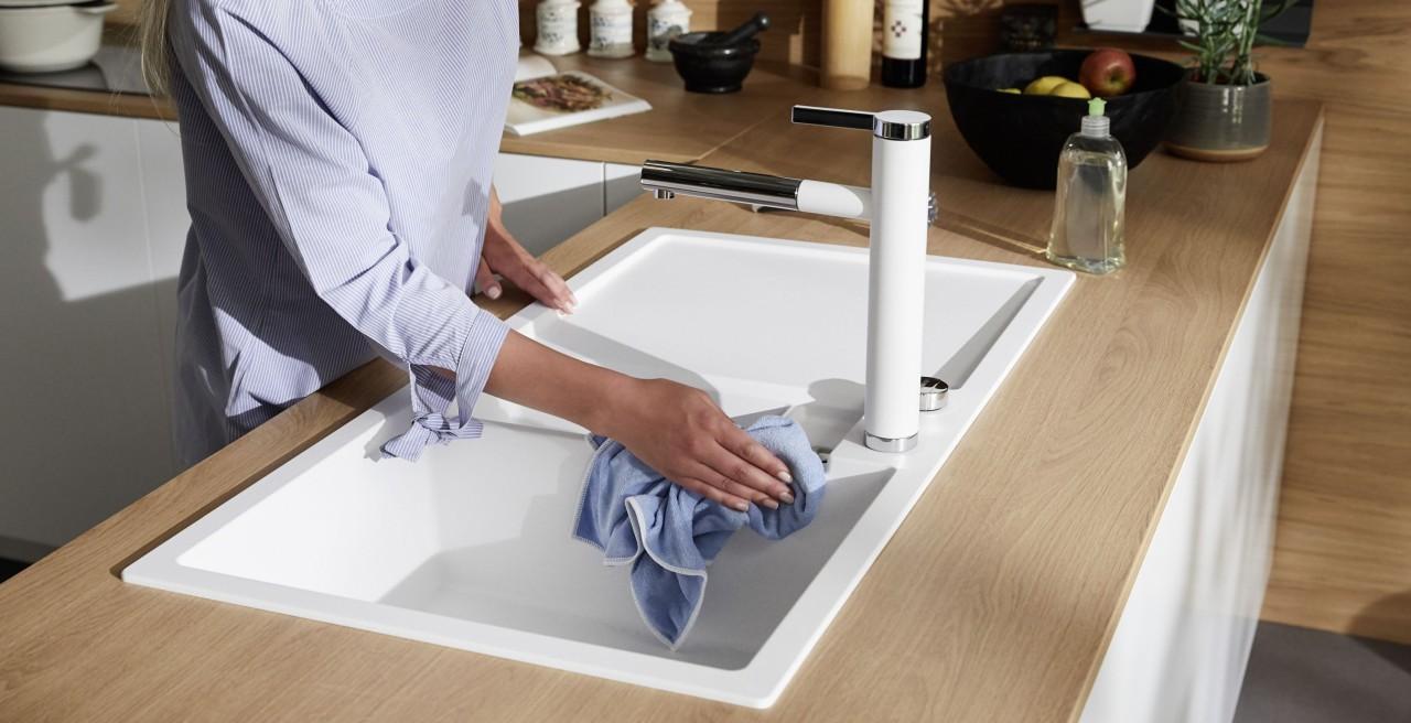 Frau reinigt Silgranit Spüle mit einem Mikrofasertuch.