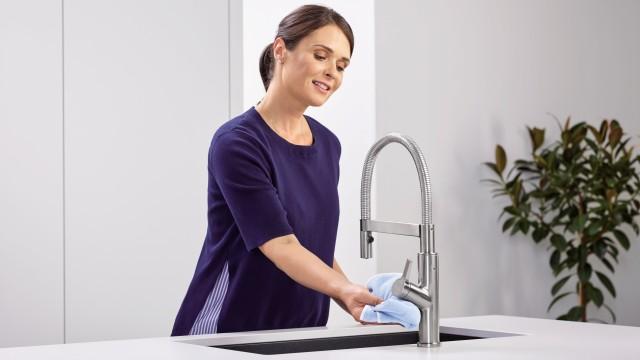Een huisvrouw maakt de mengkraan schoon met een microvezeldoek.