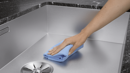 A sink made of Durinox is cleaned with a microfiber cloth