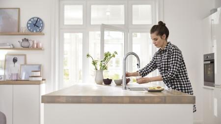 Ein Mädchen füllt ihr Wasserglas auf
