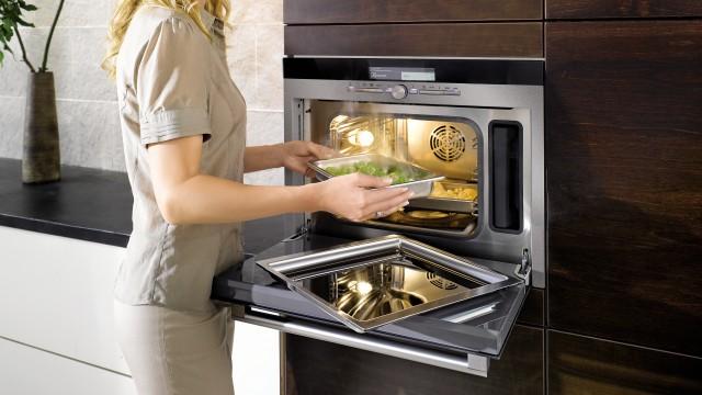 Frau benutzt Dampfgarer in der Küche