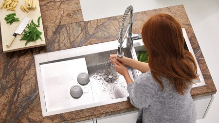 A woman washing her hands in a BLANCO ZEROX sink