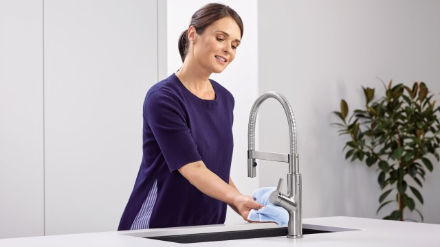 A housewife cleans the mixer tap with a microfibre cloth