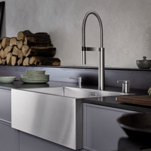 The apron front of a traditional farmhouse-style sink protrudes from the kitchen units.