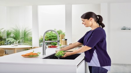 Woman standing at an undermount sink