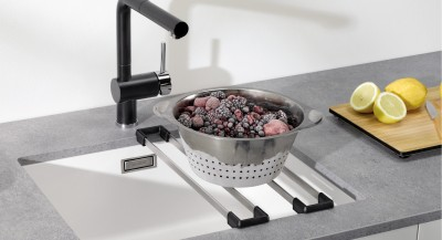 Frozen berries in a stainless steel bowl on a Blanco sink