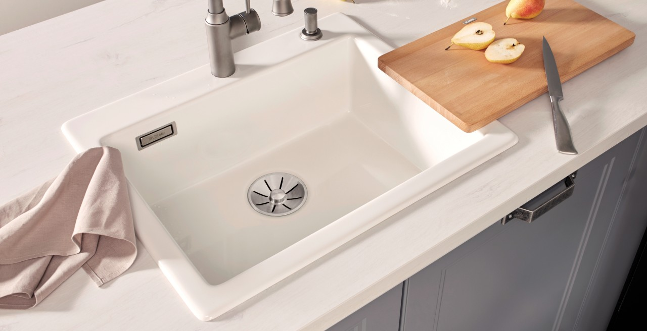 A white sink with cutting board