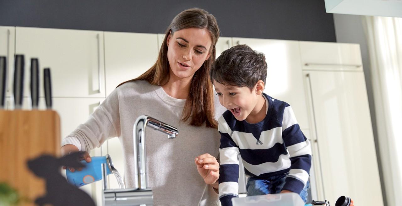 Eine Frau zeigt ihrem Sohn wie man sich richtig die Hände wäscht