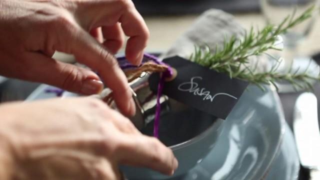 Eine Frau rückt ein Namenskärtchen auf einem Teller zurecht